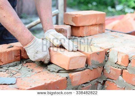 Bricklaying House Wall,  Masonry. Bricklayer Hands In Masonry Gloves Bricklaying House Wall.