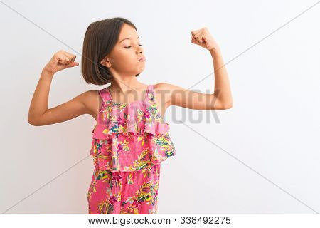 Young beautiful child girl wearing pink floral dress standing over isolated white background showing arms muscles smiling proud. Fitness concept.