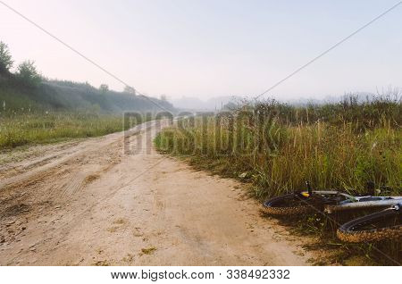 With Bike On A Country Road. A Bicycle Lies On The Side Of A Country Road. The Country Dirt Road Dis