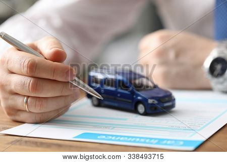 Close-up Of Businessman Hand Reading Car Insurance And Getting Ready To Sign. Small Blue Automobile