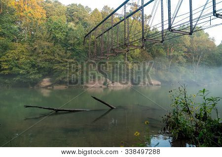 Rusted Out Abandoned Train Trestle Over The River On A Foggy Misty Morning With The Sun Rising Showi