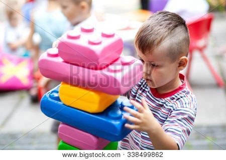 Cute Boy Playing With Buiding Toy Colorful Blocks. Kid With Happy Face Playing With Plastic Bricks.