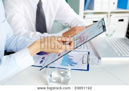 Image of human hands during discussion of business documents at meeting