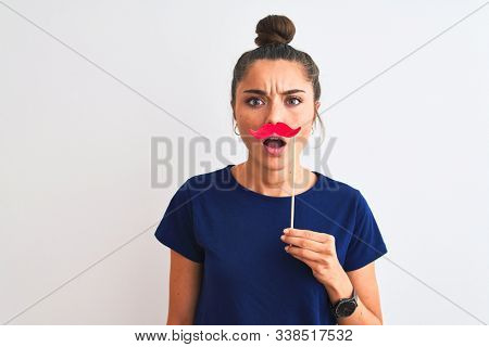Young beautiful woman holding fanny party mustache over isolated white background scared in shock with a surprise face, afraid and excited with fear expression