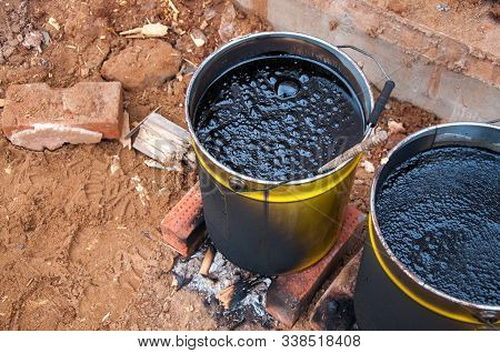 Bitumaning The Mastics In Yellow Jars. Material For Waterproofing The Foundation. The Mastika In The