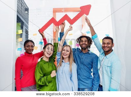Young Happy And Colorful Business Team Hold A Red Statistical Arrow. Concept Of Growing, Succesful A