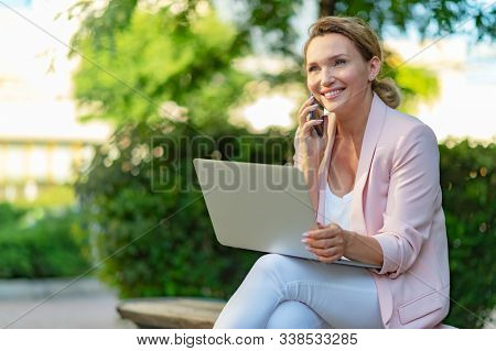 Close-up portrait of a smiling woman calling by phone on the street.  Happy businesswoman is using smart phone, outdoors. Cheerful businesswoman in a jacket with cell phone in park.