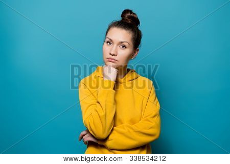 Young Woman In A Yellow Sweatshirt Thoughtfully Looks At The Camera