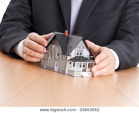 Real estate concept - businessman hands around household architectural model