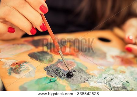 Women Hand Of The Artist With A Brush And A Palette With Oil Paints Close-up. Artist Brush Mixed Col
