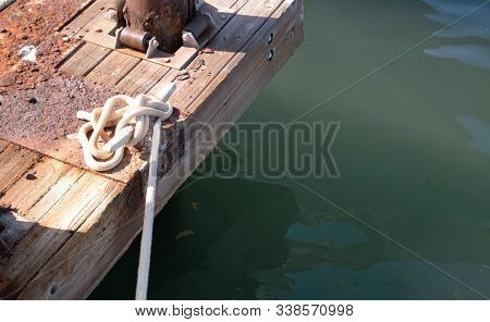 Tied Rope Knot On Wooden Dock Above Water