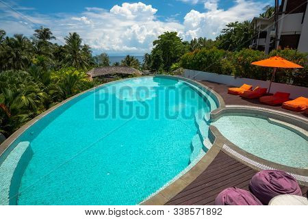 Swimming Pool With The Sunbed And Umbrella And The Cloudy Sky