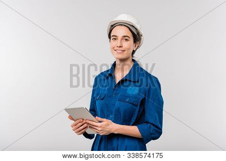 Smiling successful female engineer in workwear and hardhat using touchpad while networking in isolation