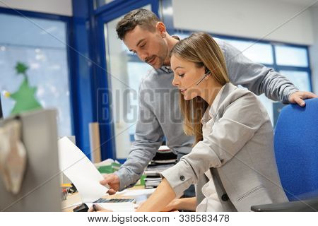 Telemarketing woman working in office with supervisor