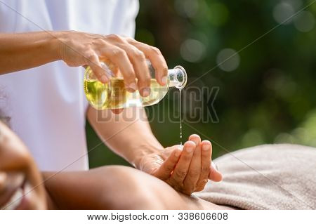 Closeup of masseuse hands pouring aroma oil on woman back. Woman prepare to do oriental spa massage for relaxing treatment. Therapist doing aromatherapy oil massage on girl body. Body care concept.