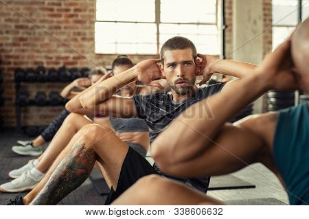 Determined young man doing exercise for abdominal. Athletic class doing abs in a row. Fitness man in gym exercising while sitting on mat in fitness center during cardio course.