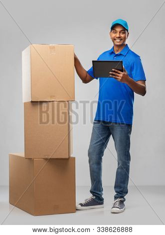 mail service, technology and shipment concept - happy indian delivery man with boxes and tablet computer in blue uniform over grey background