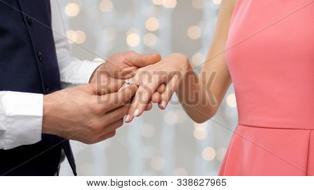 engagement, proposal and people concept - close up of man putting diamond ring on womans finger over holiday lights background