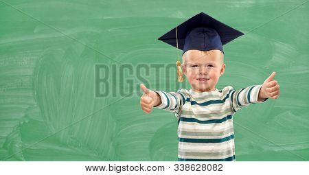 elementary school, preschool education and childhood concept - portrait of smiling little boy in mortar board showing thumbs up over green chalk board background
