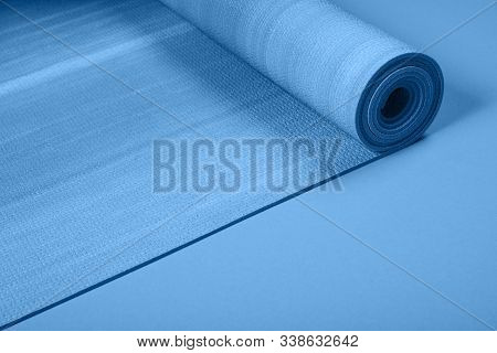 Blue Colored Exercise Mat On Background With Copy Space. Yoga Practice, Physical Workout, Pilates Or