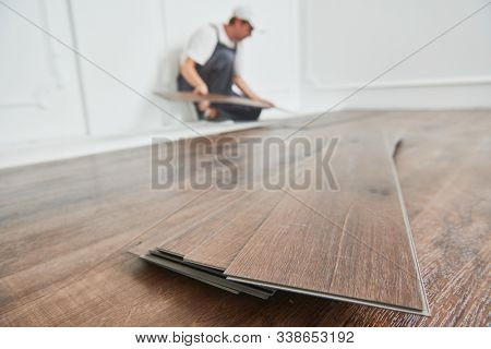 worker laying vinyl floor covering at home renovation