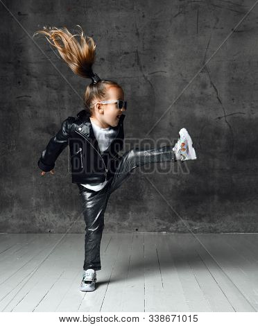 Active Frolic Cheerful Kid Girl In Leather Jacket, Pants, Shimmering Sneakers And Sunglasses Is Jump