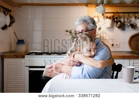 Cute Child Is Giving Gift Box To Grandmother. Kid Girl And Senior Woman Are Hugging In Cozy Kitchen
