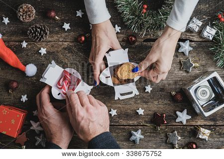 Top View Of Male And Female Hands Packing Home Made Cookies And Candy Canes In Small Gift Boxes On R