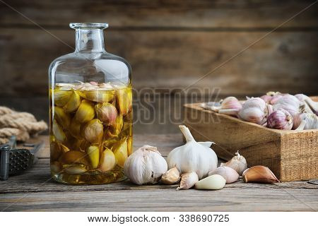 Garlic Aromatic Flavored Oil Or Infusion Bottle, Wooden Crate Of Garlic Cloves And  Garlic Press On
