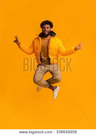 Peaceful Winter African Guy Demonstrating Peace Symbol While Jumping, Orange Background
