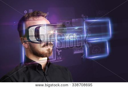 Businessman looking through Virtual Reality glasses with VIRTUAL REALITY inscription, new technology concept