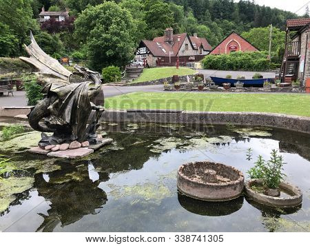 Tintern, Monmouthshire, Wales. June 9  2019. Abbey Mill in the Wye Valley with pond & bronze Dragon Sculpture. Ancient site near the town of Tintern & the historical Cistercian Abbey.