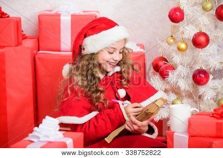 Girl Little Kid Hold Pen And Paper Near Christmas Tree Writing Letter. Child Write Letter To Santa C