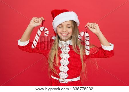 Best Christmas Decor. Happy Kid Hold Candy Canes. Little Girl With Xmas Decorations. Candy Cane Chri