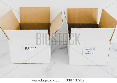 Decluttering Concept, Storage Boxes To Sort Between Objects To Keep And Those To Declutter Or Donate