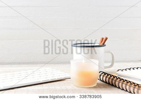 White mug with cinammon sticks on a home office desk, with candle, keyboard, and note pad. Horizontal with copy space.