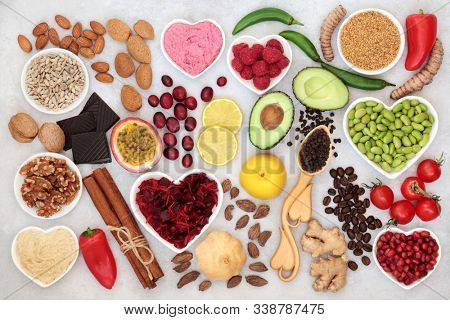 Healthy heart food for vitality with fruit, vegetables, nuts, dips, spice & herbs, high in fibre, antioxidants, vitamins, omega 3 & protein. Support for the cardiovascular system with low GI. Flat lay