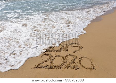 New Years 2020 replace 2019 concept. End of 2019 Happy New Year 2020, lettering on beach