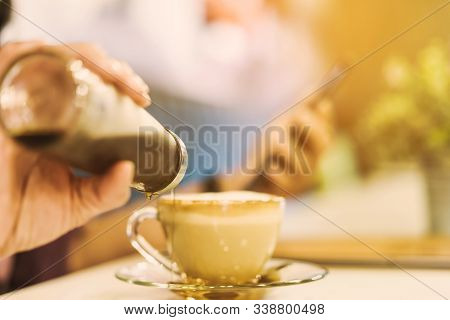 A Woman Poured The Syrup Into The Saucer Of The Coffee Cup While Absent-mindedly Playing The Smartph