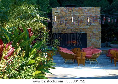 Contemporary Style Outdoor Patio Furniture Besides A Fireplace And Lush Plants Taken In A Garden Wit