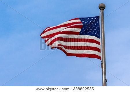Usa Flag From Flagstaff Waving Over Blue Sky Background, United States, Independence Day Concept