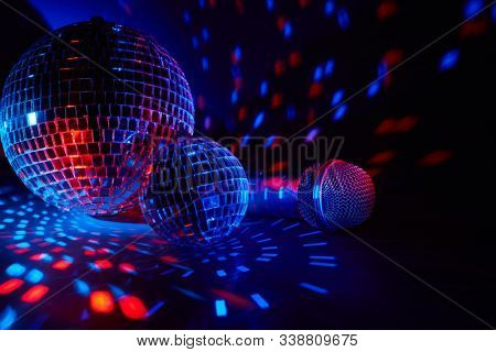 Glittering mirror disco balls and microphone on dark background with red blue lighting. Copy space.  Weekend or holiday party. Karaoke club. For advertising or web design.