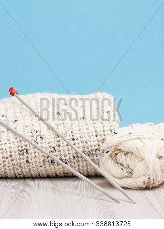 Woolen Pullover And Yarn For Knitting. Skeins Of Natural Wool Yarn And Knitting Needles