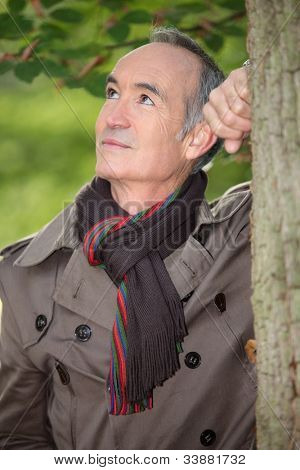 Retired man leaning against a tree