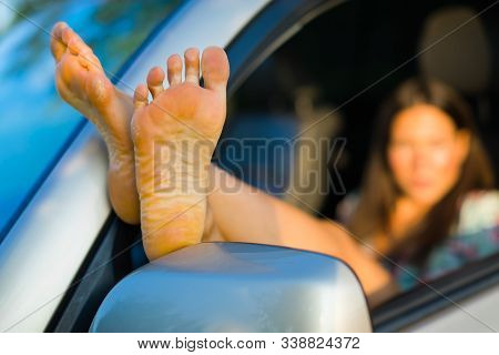 Seductive Woman Having Exposed Bare Feet Out Of Car Window, Focus On Sole