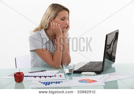 Young woman pensive in front of laptop computer
