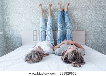 A Young Married Couple Lies On The Bed, Legs To The Wall And Looks At The Ceiling, The Relationship