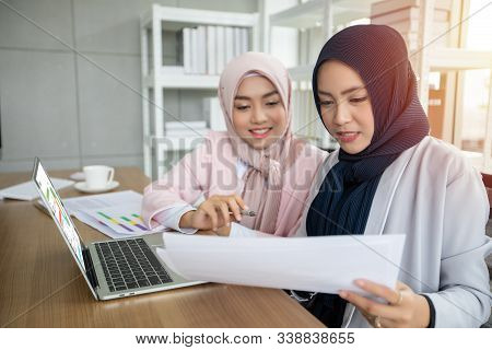 Muslim Business Woman In Traditional Clothing Working And Discussing At Meeting In Office.