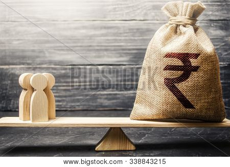 Indian Rupee Inr Symbol On Money Bag And People On Scales. Concept Attracting Investment, Business C