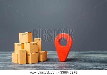 Red Location Pointer Geolocation Symbol And Cardboard Boxes. Distribution Delivery Of Goods, Freight